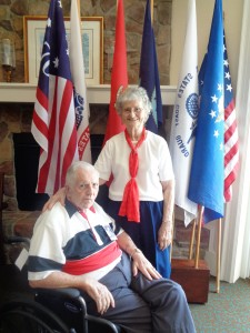 Resident and veteran Larry Nanns and his wife Jean pose in front of the American and military flags.