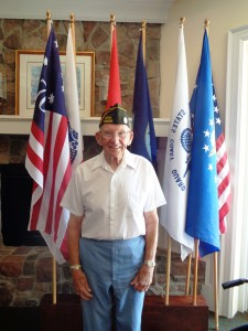Veteran Dick Winslow stands proudly before the American flag.